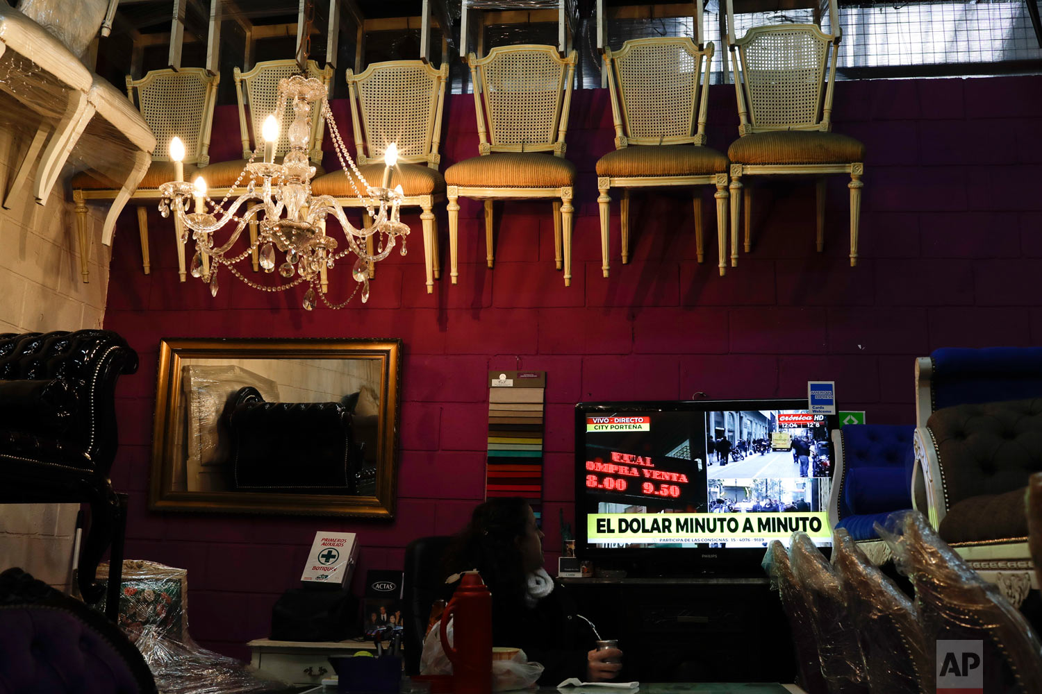 In this Aug. 30, 2018 photo, a woman watches the news on the value of the Argentine peso versus the U.S. dollar in Buenos Aires, Argentina. Inflation is killing the purchasing power of Argentines whose rate of around 45 percent is one of the world's worst. (AP Photo/Natacha Pisarenko)