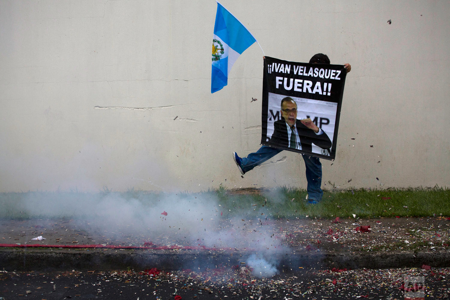 In this Aug. 31, 2018 photo, a supporter of the president's decision to shut down an anti-graft commission protests amid fire crackers outside the U.N. International Commission Against Impunity (CICIG) office in Guatemala City. The government reiterated in Sept. it is refusing to readmit Ivan Velasquez, head of a U.N. commission investigating corruption. (AP Photo/Moises Castillo)