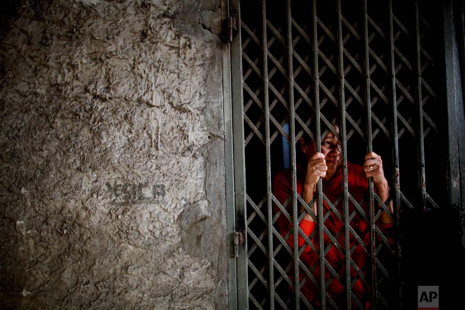 In this Sept. 6, 2018 photo, Modesta Cabanas stands behind her home's security gate on the outskirts of Buenos Aires, Argentina. Cabanas feeds her family at a soup kitchen, and says that since Argentina's economic crisis started, the portions are much smaller because more people are eating there. (AP Photo/Natacha Pisarenko)