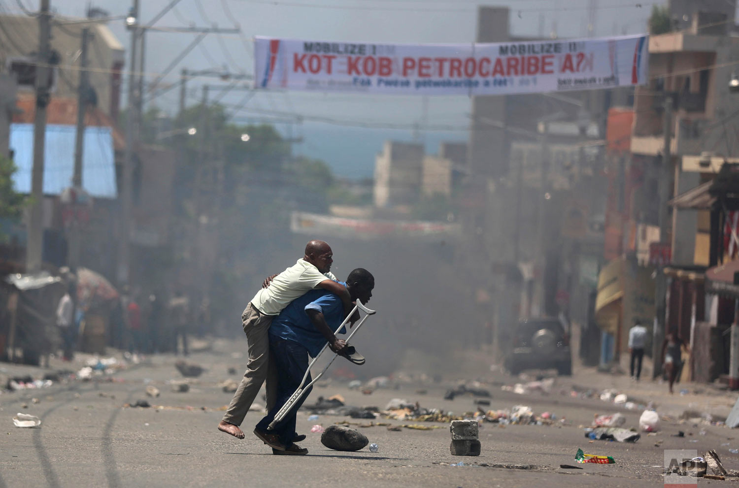 In this Sept. 9, 2018 photo, a handicapped man on crutches is carried amid police tear gas as protesters demand to know how the government spent Petro Caribe funds, intended to help Haiti rebuild after the 2010 earthquake, in Port-au-Prince, Haiti. Protesters say projects are unfinished and officials inflated costs to steal money. (AP Photo/Dieu Nalio Chery)