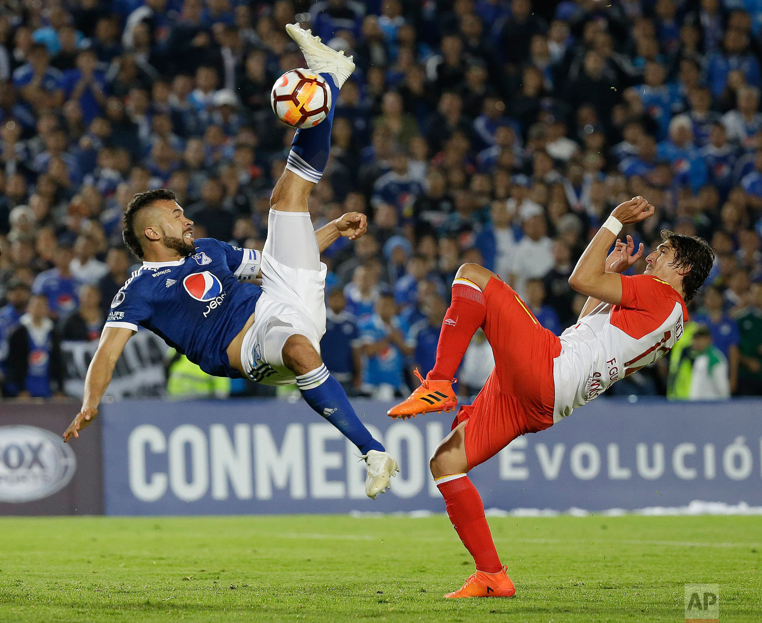 In this Oct. 2, 2018 photo, Andres Cadavid of Colombia's Millonarios kicks the ball past Facundo Guichon of Colombia's Independiente Santa Fe during a Copa Sudamericana soccer match in Bogota, Colombia. (AP Photo/Fernando Vergara)