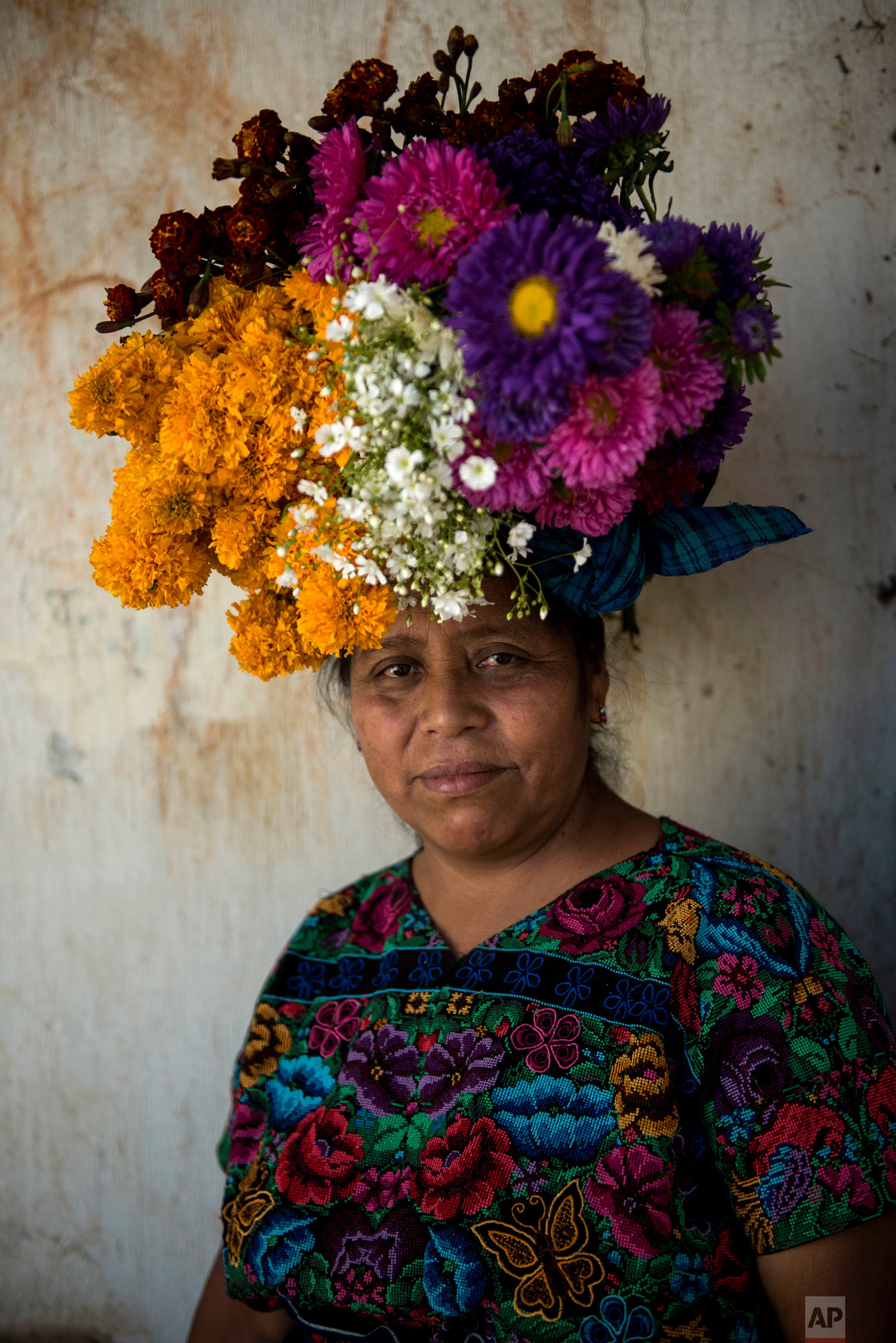 In this Nov. 1, 2018 photo, Olga Socorec balances flowers on her head as she poses for a portrait while decorating the tombs of family members, including her father's, during Day of the Dead celebrations at the cemetery in Santiago Sacatepequez, Guatemala. (AP Photo/Oliver de Ros)