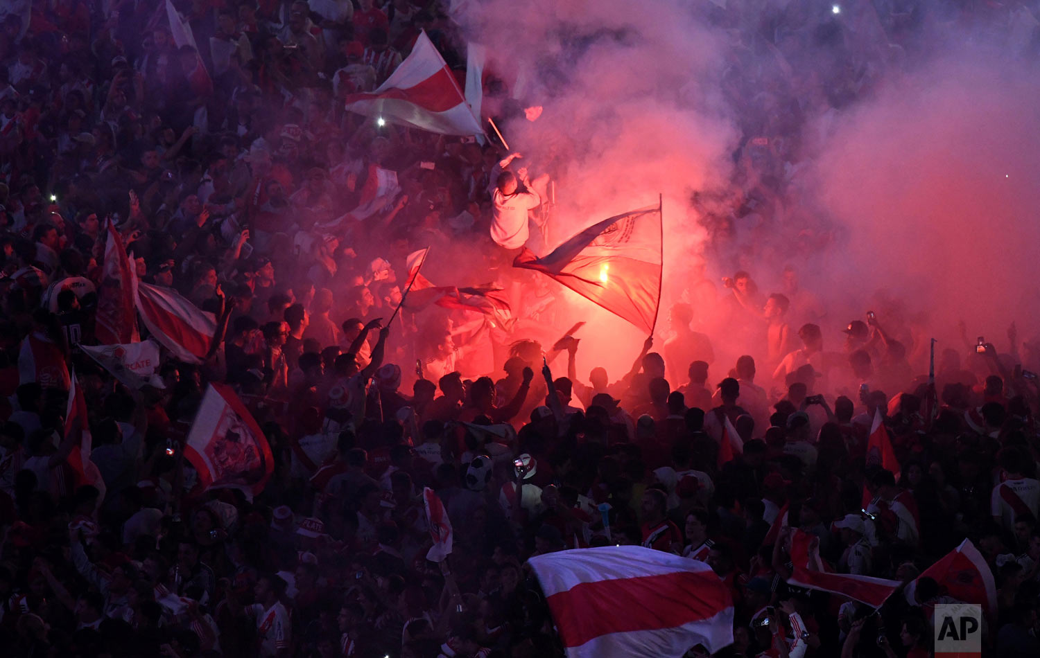 In this Dec. 9, 2018 photo, River Plate soccer fans celebrate their team's 3-1 victory over Boca Juniors and clenching the Copa Libertadores championship title, at the Obelisk in Buenos Aires, Argentina. (AP Photo/Gustavo Garello)