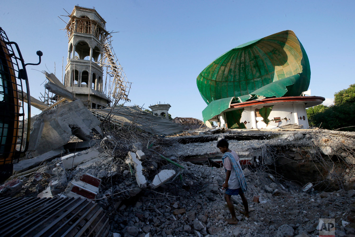 A resident inspects a mosque damaged by an earthquake in North Lombok, Indonesia, on Aug. 7, 2018. (AP Photo/Tatan Syuflana)