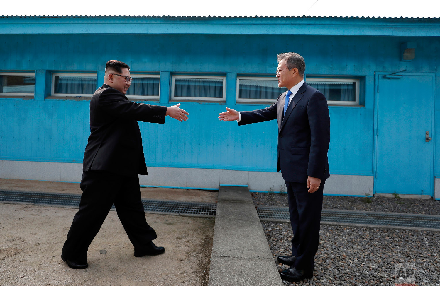 North Korean leader Kim Jong Un, left, prepares to shake hands with South Korean President Moon Jae-in over the military demarcation line at the border village of Panmunjom in Demilitarized Zone on April 27, 2018. (Korea Summit Press Pool via AP)