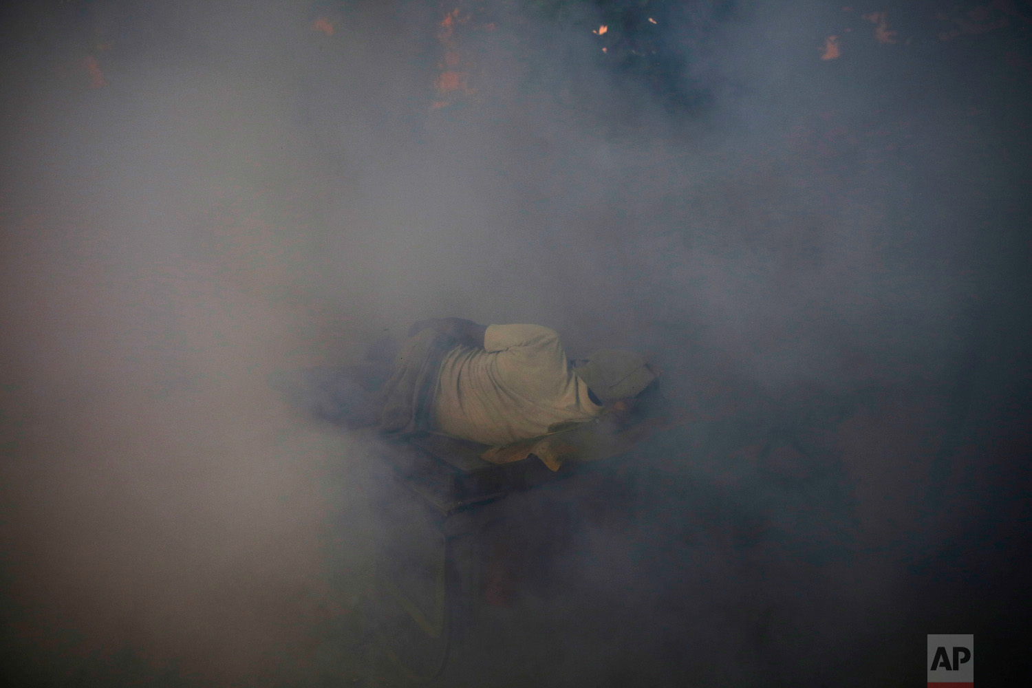 A man sleeps on a cart surrounded by smoke from fumigation, being carried out to prevent the spread of mosquito-borne diseases in Allahabad, India, on Sept. 13, 2018. (AP Photo/Rajesh Kumar Singh)
