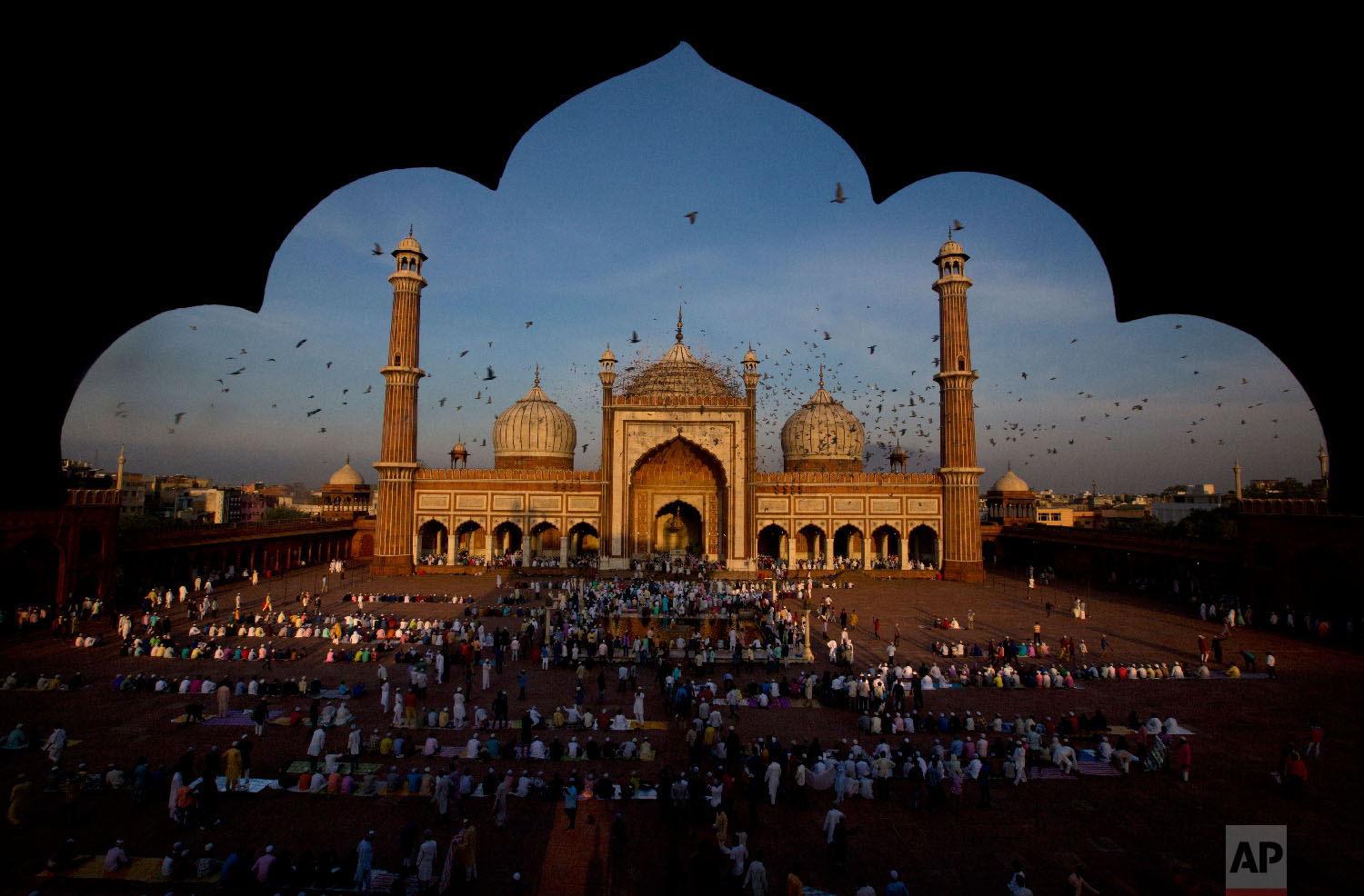 Pigeons fly past as Muslims gather to offer Eid al-Adha prayers at Jama Masjid in New Delhi, India, on Aug. 22, 2018. (AP Photo/Manish Swarup)
