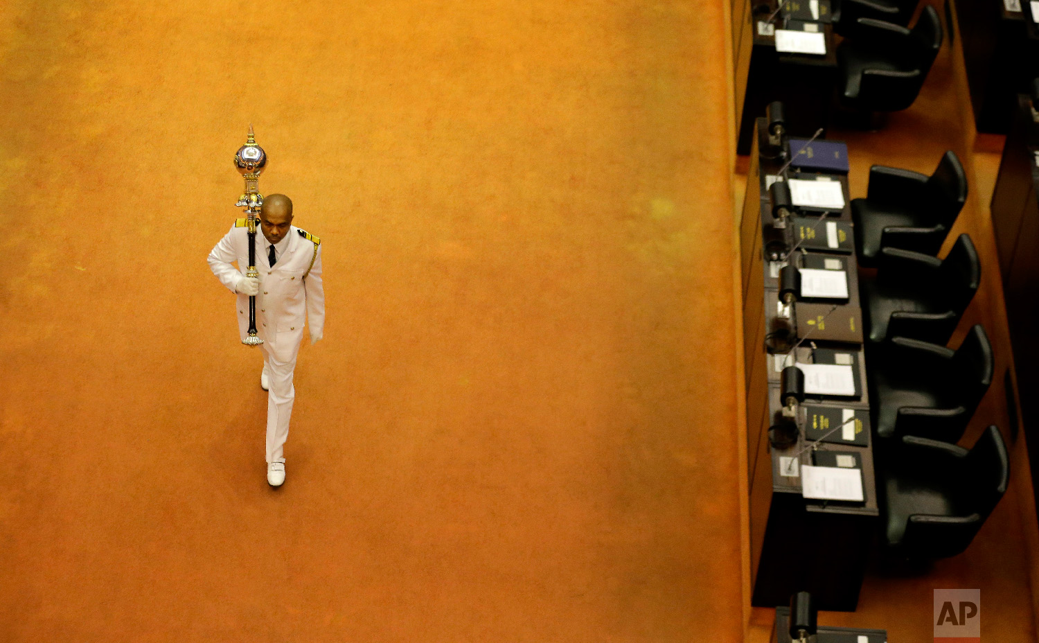 Sri Lanka's sergeant at arms Narendra Fernando walks carrying the mace in the well of the house past empty seats of President Maithripala Sirisena and disputed Prime Minister Mahinda Rajapaksa at the beginning of the parliamentary session in Colombo, Sri Lanka, on Dec. 5, 2018. (AP Photo/Eranga Jayawardena)