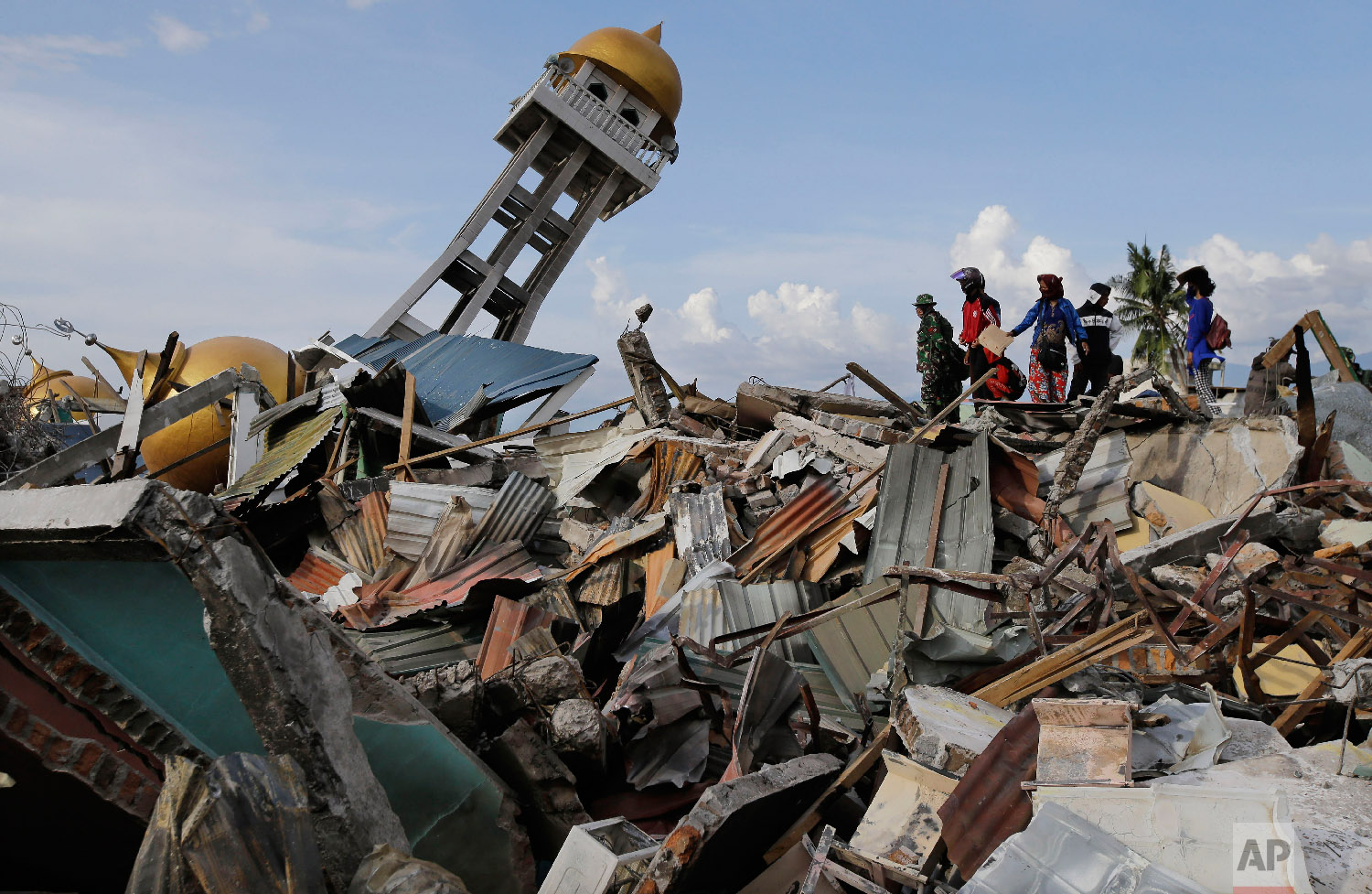 Rescuers and villagers wait for news for their missing loved one's as recovery efforts continue after liquefaction hit the neighborhood of Balaroa in Palu, Central Sulawesi, Indonesia, on Oct. 6, 2018. (AP Photo/Aaron Favila)