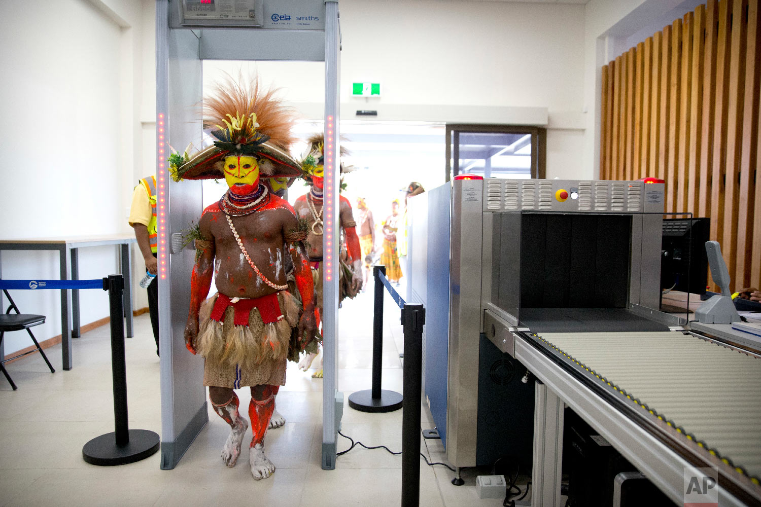 Performers in traditional dresses pass through a security screening at Jacksons International Airport in Port Moresby, Papua New Guinea, ahead of a visit by U.S. Vice President Mike Pence, Saturday, Nov. 17, 2018. (AP Photo/Mark Schiefelbein)