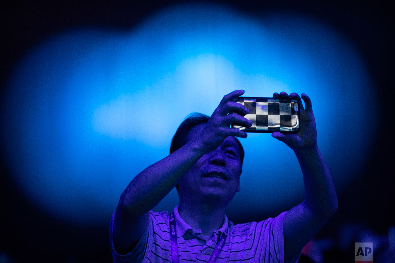 A spectator takes a cellphone photo of the CHAIN Cup at the China National Convention Center in Beijing, Saturday, June 30, 2018. A computer running artificial intelligence software defeated two teams of human doctors in accurately recognizing maladies in magnetic resonance images on Saturday, in a contest that was billed as the world's first competition in neuroimaging between AI and human experts. (AP Photo/Mark Schiefelbein)