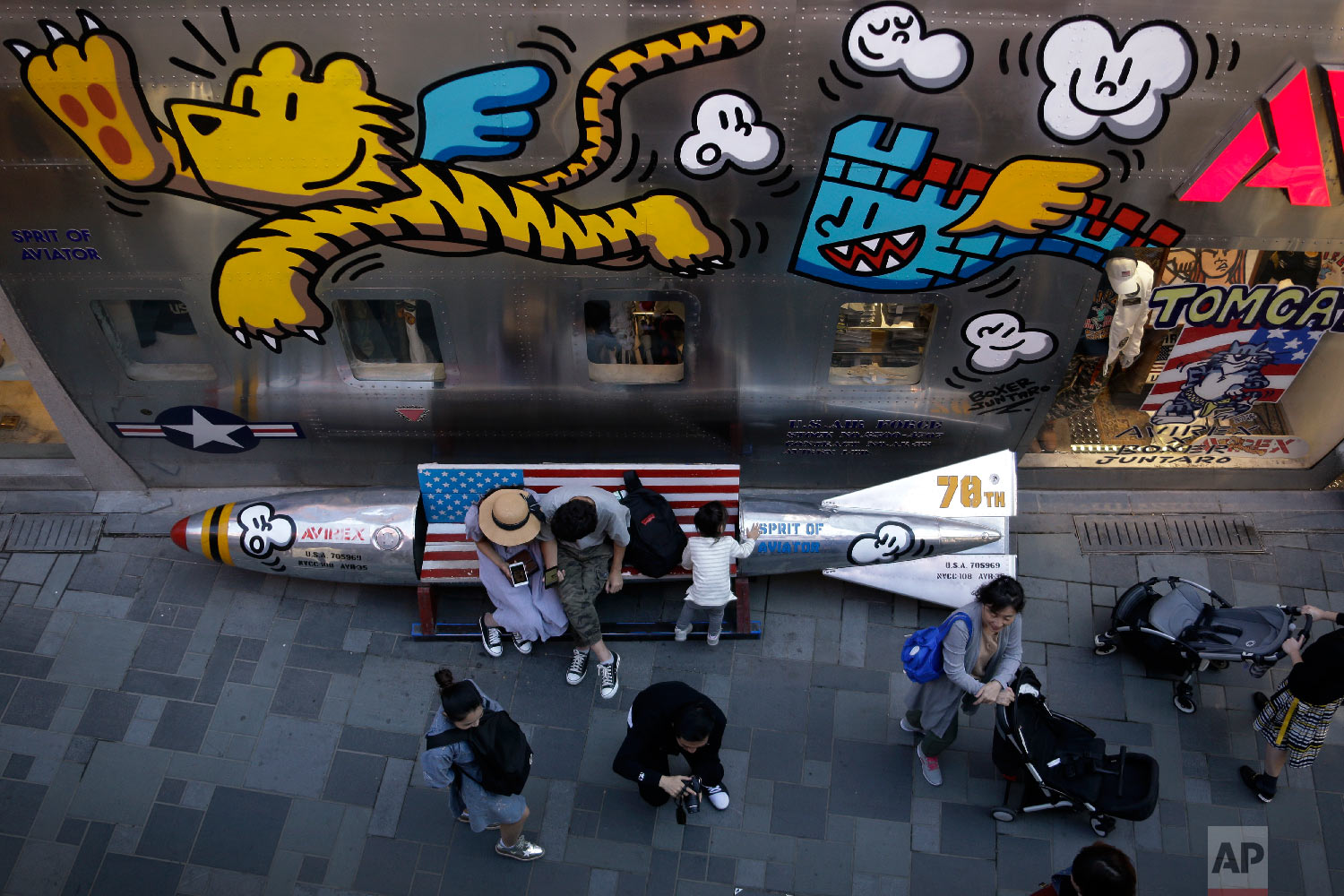 Shoppers spend their time near a bench in a shape of a mocked aerial bomb and a U.S. flag outside a fashion boutique selling U.S. brand clothing at the capital city's popular shopping mall in Beijing, Monday, Sept. 24, 2018. China raised tariffs Monday on thousands of U.S. goods in an escalation of its fight with President Donald Trump over technology policy and accused Washington of bullying Beijing and damaging the global economy. (AP Photo/Andy Wong)