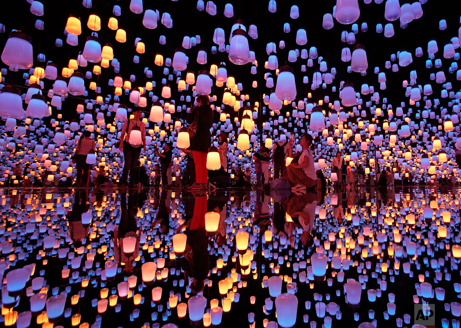 "Visitors walk through the installation of ""Forest of Resonating Lamps"" at the Mori Building Digital Art Museum in Tokyo, Thursday, June 21, 2018. Mori Building, a Japanese real estate company and teamLab, digital art collective company, have joined together to create the digital art museum in Tokyo. ""MORI Building DIGITAL ART MUSEUM: teamLab Borderless'"" exhibition displayed 50 interactive artworks in a 10,000 square-meter space. (AP Photo/Shuji Kajiyama)"