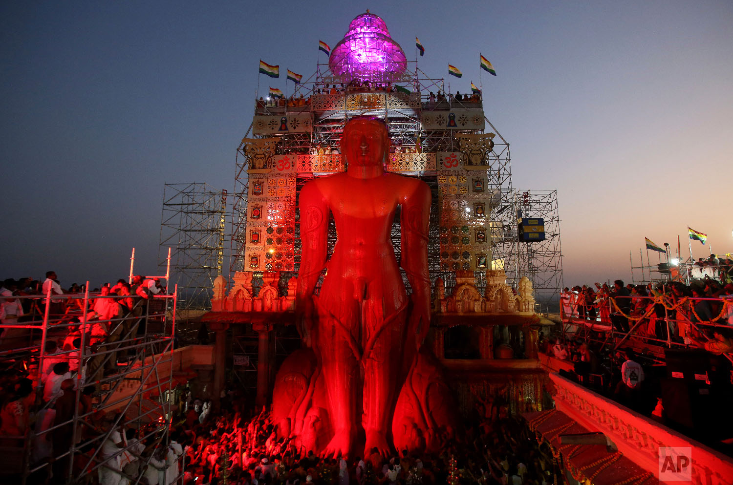 Vermilion runs down the 58.8-foot monolithic statue of Jain god Gomateshwara at Shravanabelagola 145 kilometers (91 miles) west of Bangalore, India, Saturday, Feb. 17, 2018. Hundreds of thousands of Jain devotees will attend the Mahamastabhisheka or head anointing ceremony of the 1,037-year-old statue Gomateswara (Lord Bahubali), a tradition held every 12 years since AD 981. The 1,037-year-old statue is bathed with milk, turmeric, vermilion, saffron, sandalwood paste, powder of medicinal herbs and gold coins. (AP Photo/Aijaz Rahi)