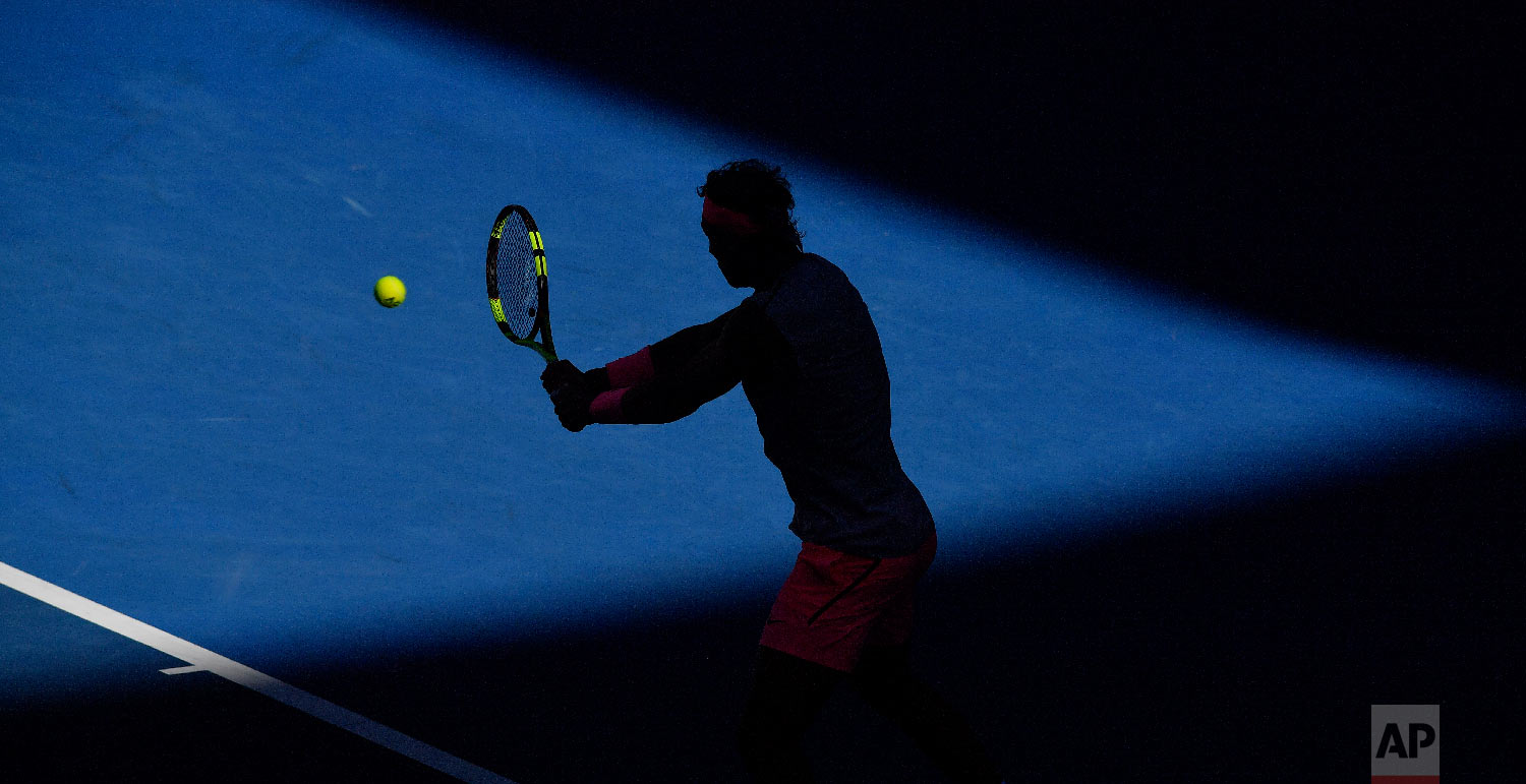 Spain's Rafael Nadal is silhouetted as he makes a backhand to Argentina's Leonardo Mayer during their second round match at the Australian Open tennis championships in Melbourne, Australia, Wednesday, Jan. 17, 2018. (AP Photo/Andy Brownbill)