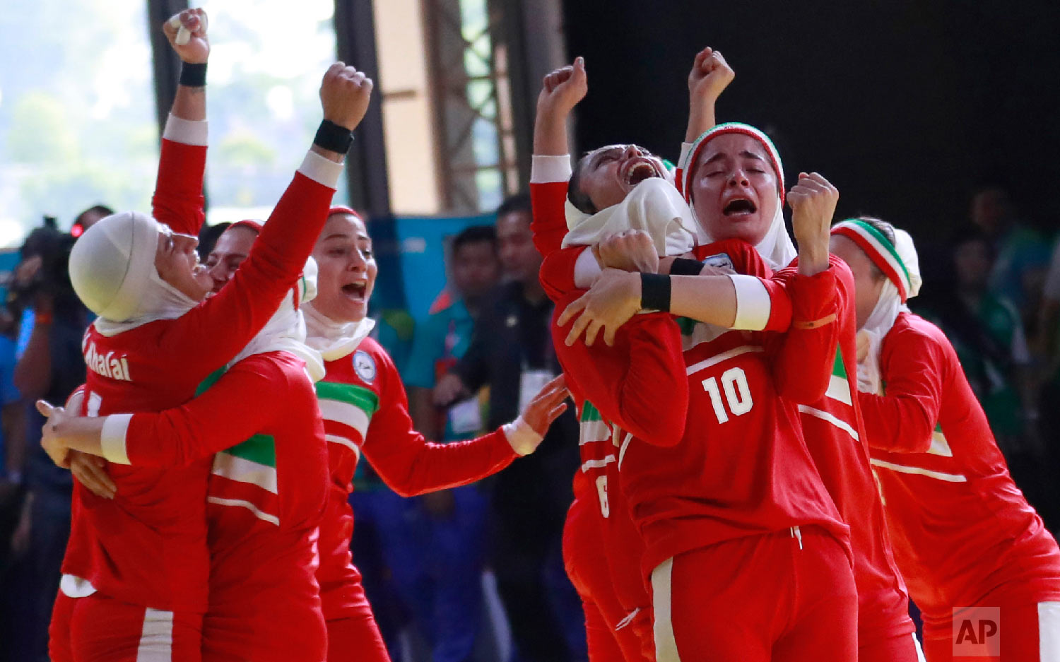 Iran's team, in red, react after defeating India's during at the women's team Kabaddi gold medal match at the 18th Asian Games in Jakarta, Indonesia, Friday, Aug. 24, 2018. Iran won gold.(AP Photo/Tatan Syuflana)
