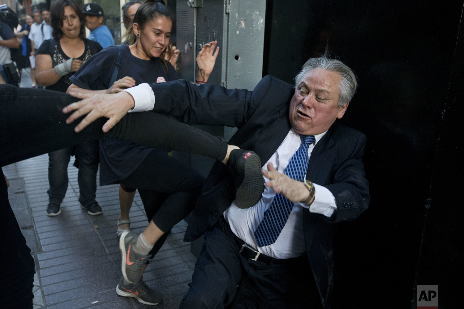Ivan Arostica, president of Chile's Constitutional Court (TC), is kicked by a protester as he leaves the court which listened to arguments in favor and against conditional freedom for those convicted of human rights crimes in Santiago, Chile, on Wednesday, Dec. 19, 2018. Protesters fear a ruling in favor could benefit the prisoners of Punta Peuco, a prison for state agents convicted of murder during the dictatorship of Augusto Pinochet (1973-1990). (AP Photo/Esteban Felix)