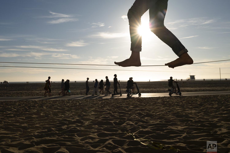 Vladimir Kozlov, 32, foreground, balances on a slackline at the beach in Santa Monica, Calif., on Thursday, Dec. 20, 2018. (AP Photo/Jae C. Hong)