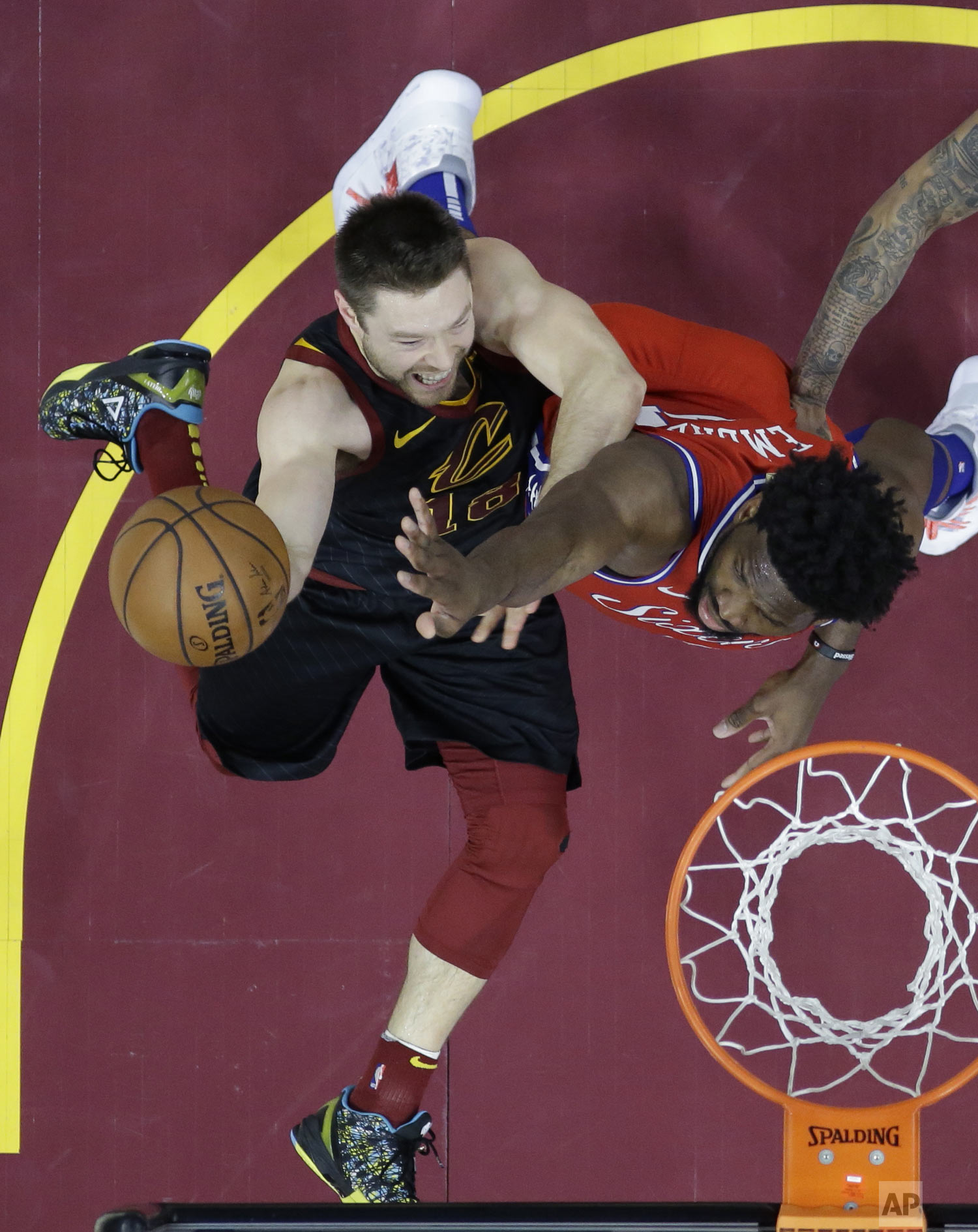 Cleveland Cavaliers' Matthew Dellavedova (18) shoots against Philadelphia 76ers' Joel Embiid (21), from Cameroon, during the first half of an NBA basketball game Sunday, Dec. 16, 2018, in Cleveland. (AP Photo/Ron Schwane)