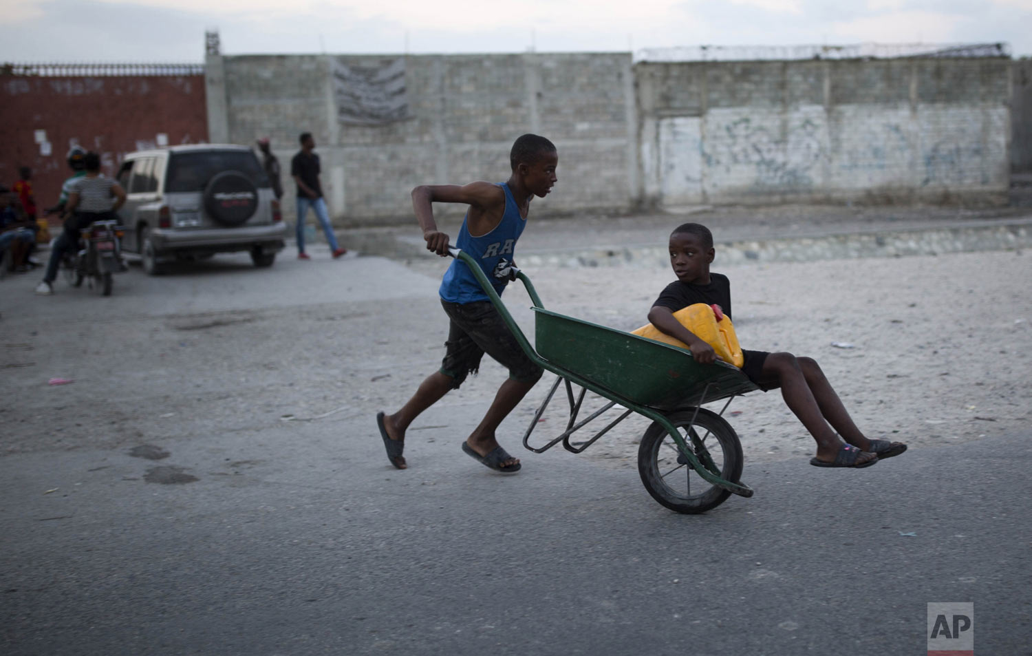 Brothers head to a public fountain with a wheelbarrow to fill their container with water to use at home to drink, cook and bathe, in the Cite Soleil slum of Port-au-Prince, Haiti, Tuesday, Dec. 18, 2018. (AP Photo/Dieu Nalio Chery)