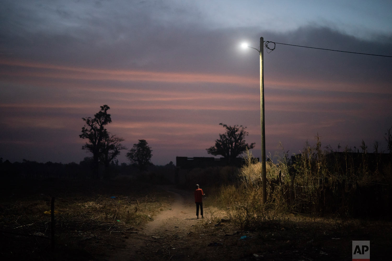 A boy stand under a street lamp at dusk on Nov. 26, 2018, in a village near Goudiry, Senegal. (AP Photo/Felipe Dana)