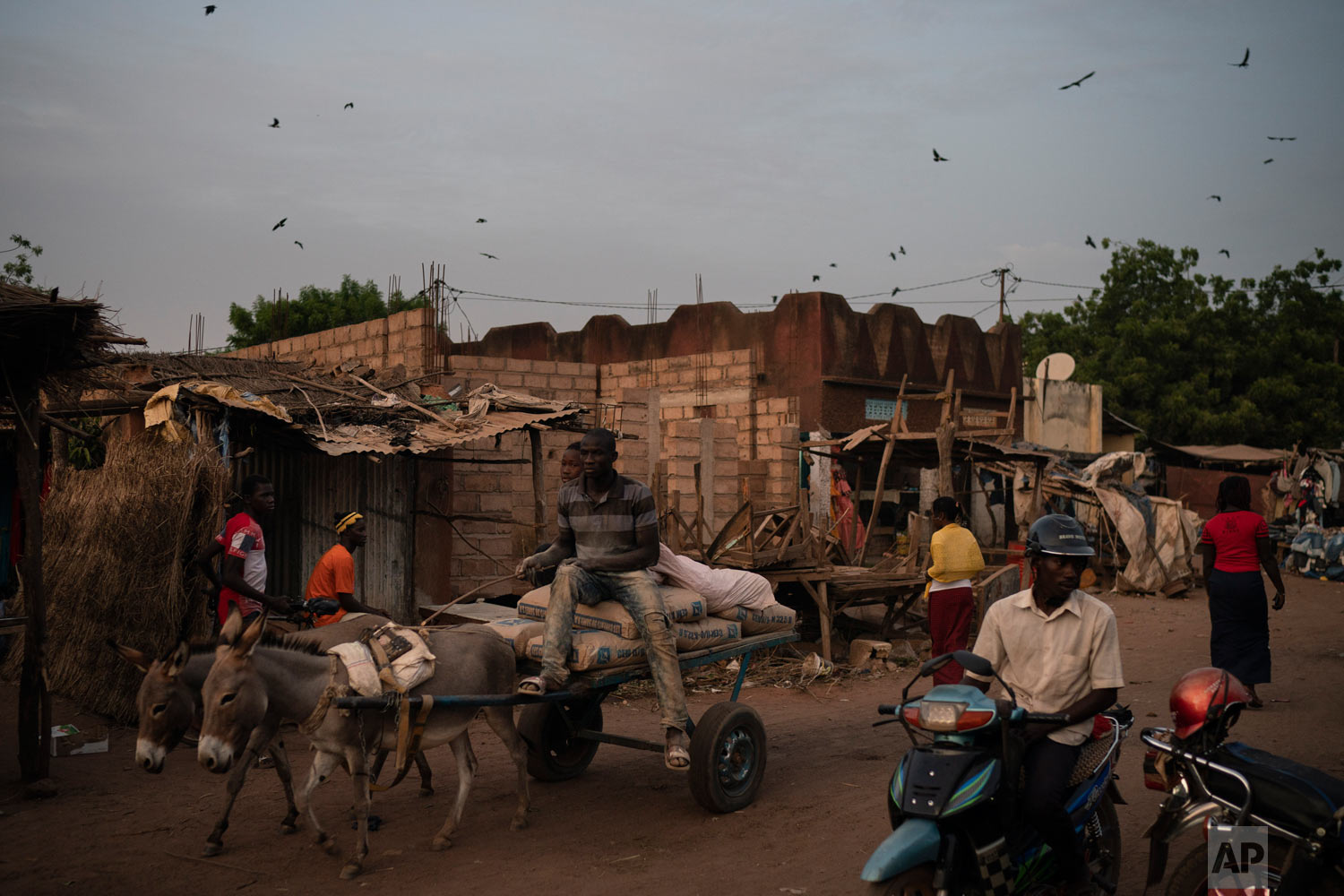 A man rides his motorcycle as people walk on a street on Nov. 26, 2018, in Goudiry, Senegal. (AP Photo/Felipe Dana)