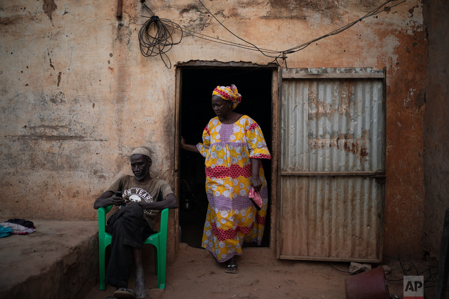 Cheikh Fofana sits in his house as his wife Khadiatou Toure, right, walks by on Nov. 25, 2018, in Goudiry, Senegal. (AP Photo/Felipe Dana)