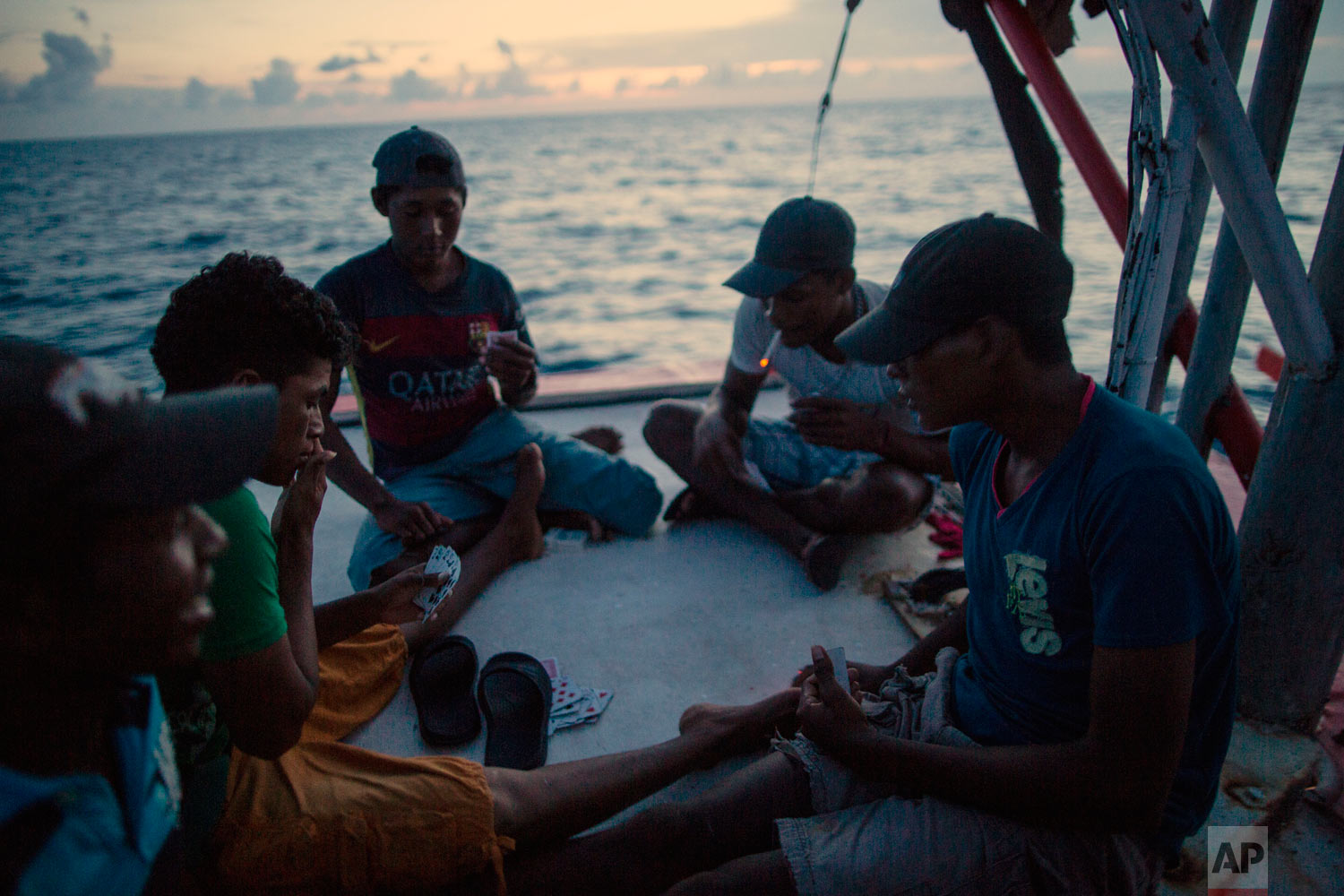 In this Sept. 10, 2018 photo, Miskito divers play a game of cards on a ship's stern as they are transported home after a two week fishing trip, near the Savannah Cay, Honduras. (AP Photo/Rodrigo Abd)