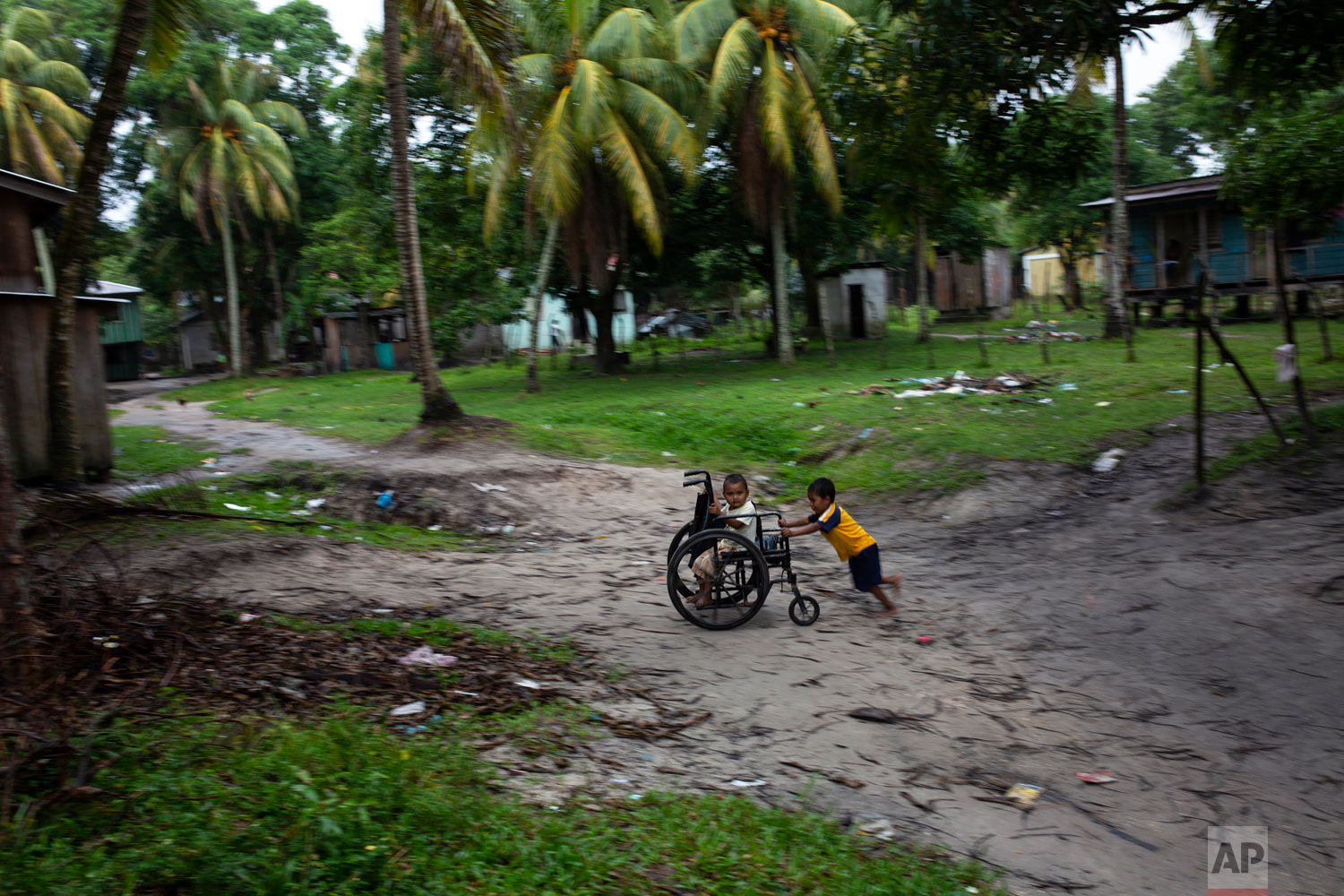 In this Feb. 6, 2018 photo, Charles Melendez, 5, and his 4-year-old brother Jefferson, play with their father's wheelchair while he rests, in Puerto Lempira, Honduras. (AP Photo/Rodrigo Abd)