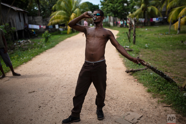 In this Feb 1, 2018 photo, Angel Ponce takes a swig of rum, in Puerto Lempira, Honduras. (AP Photo/Rodrigo Abd)