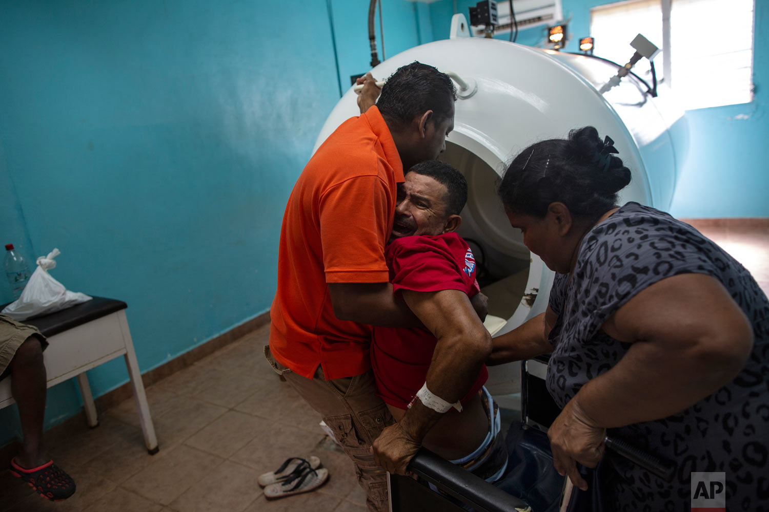 In this Feb. 9, 2018 photo, paralyzed by decompression sickness, lobster diver Misael Banegas Diaz, 49, is lifted by physical therapist Cedrak Waldan Mendoza into a hyperbaric chamber at the hospital in Puerto Lempira, Honduras. (AP Photo/Rodrigo Abd)