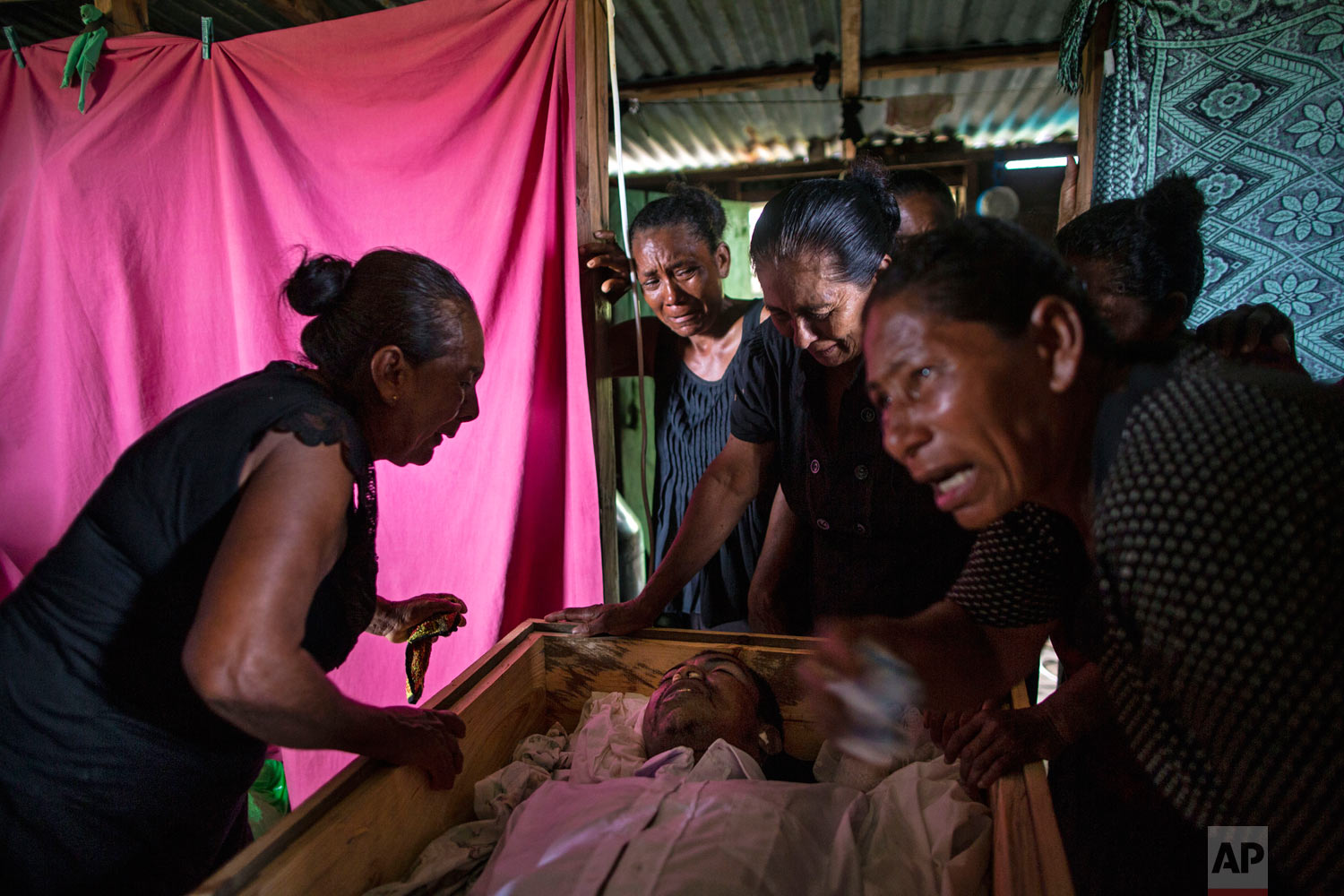 In this Sept. 2, 2018 photo, Sonia Wills, left, accompanied by relatives, mourns over the coffin that contain the remains of her son, Miskito diver Oscar Salomon Charly, 31, during a wake in her home, in Cabo Gracias a Dios, Nicaragua. (AP Photo/Rodrigo Abd)