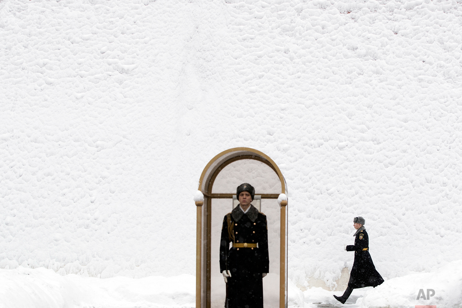 An Honor guard soldier walks along the Kremlin Wall, covered by snow, as his fellow soldier stands at the Tomb of Unknown Soldier in Moscow, Russia, Wednesday, Jan. 31, 2018. (AP Photo/Pavel Golovkin)