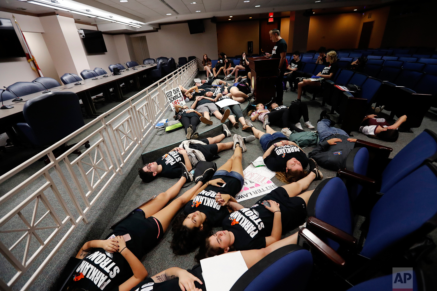 Seventeen student survivors from Marjory Stoneman Douglas High School lie down on the floor in silence and pray at the approximate time of the attack one week ago, inside the state capitol, in Tallahassee, Fla., Wednesday, Feb. 21, 2018. The students, members of the Congregation Kol Tikvah Temple, lost three students, and were at the capitol to pressure lawmakers on gun control reform. (AP Photo/Gerald Herbert)