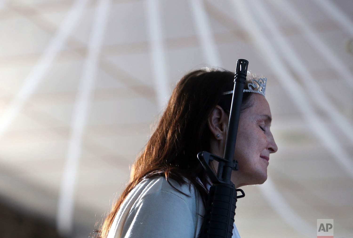 A standing woman closes her eyes as she holds an unloaded weapon during services at the World Peace and Unification Sanctuary, Wednesday Feb. 28, 2018, in Newfoundland, Pa. Worshippers clutching AR-15 rifles participated in a commitment ceremony at the Pennsylvania-based church. (AP Photo/Jacqueline Larma)