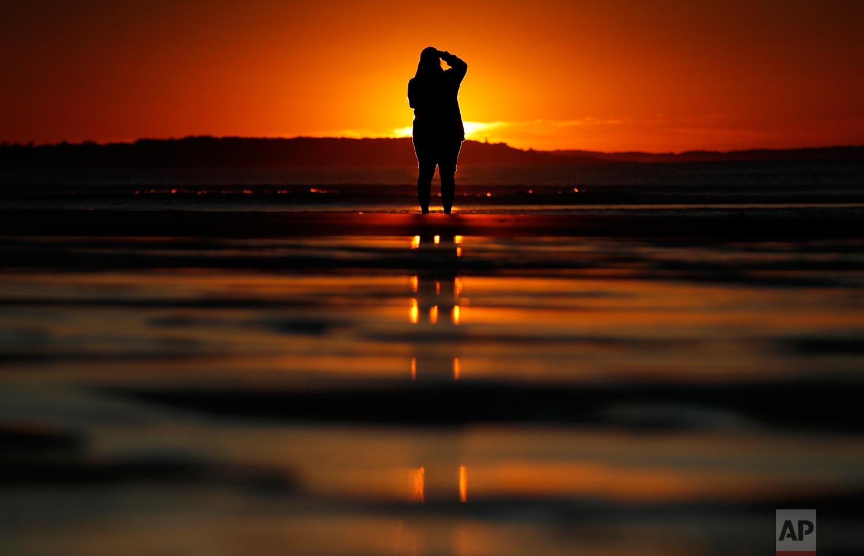 Consuello Jessop, of Providence, R.I., photographs the sunrise at Ocean Park, Thursday, July 12, 2018, in Old Orchard Beach, Maine. (AP Photo/Robert F. Bukaty)