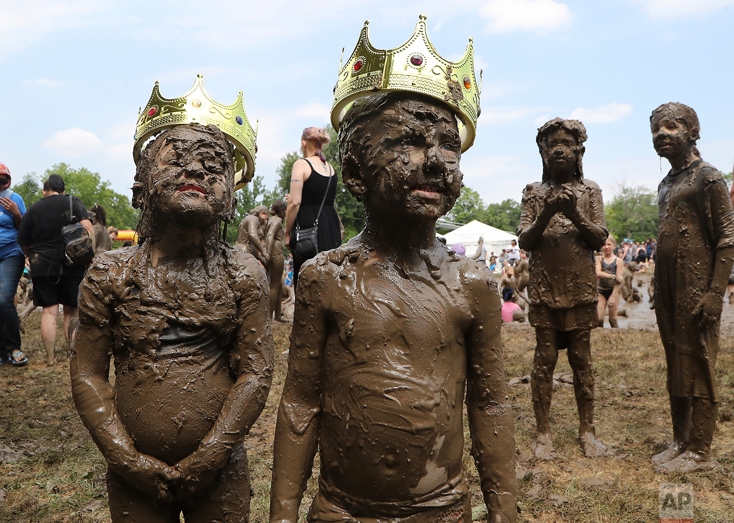 Molly Kofahl, 4, left, and Charles Daviskiba, 3, pose after being crowned Mud Day Queen and King during Mud Day at the Nankin Mills Park, Tuesday, July 10, 2018, in Westland, Mich. (AP Photo/Carlos Osorio)