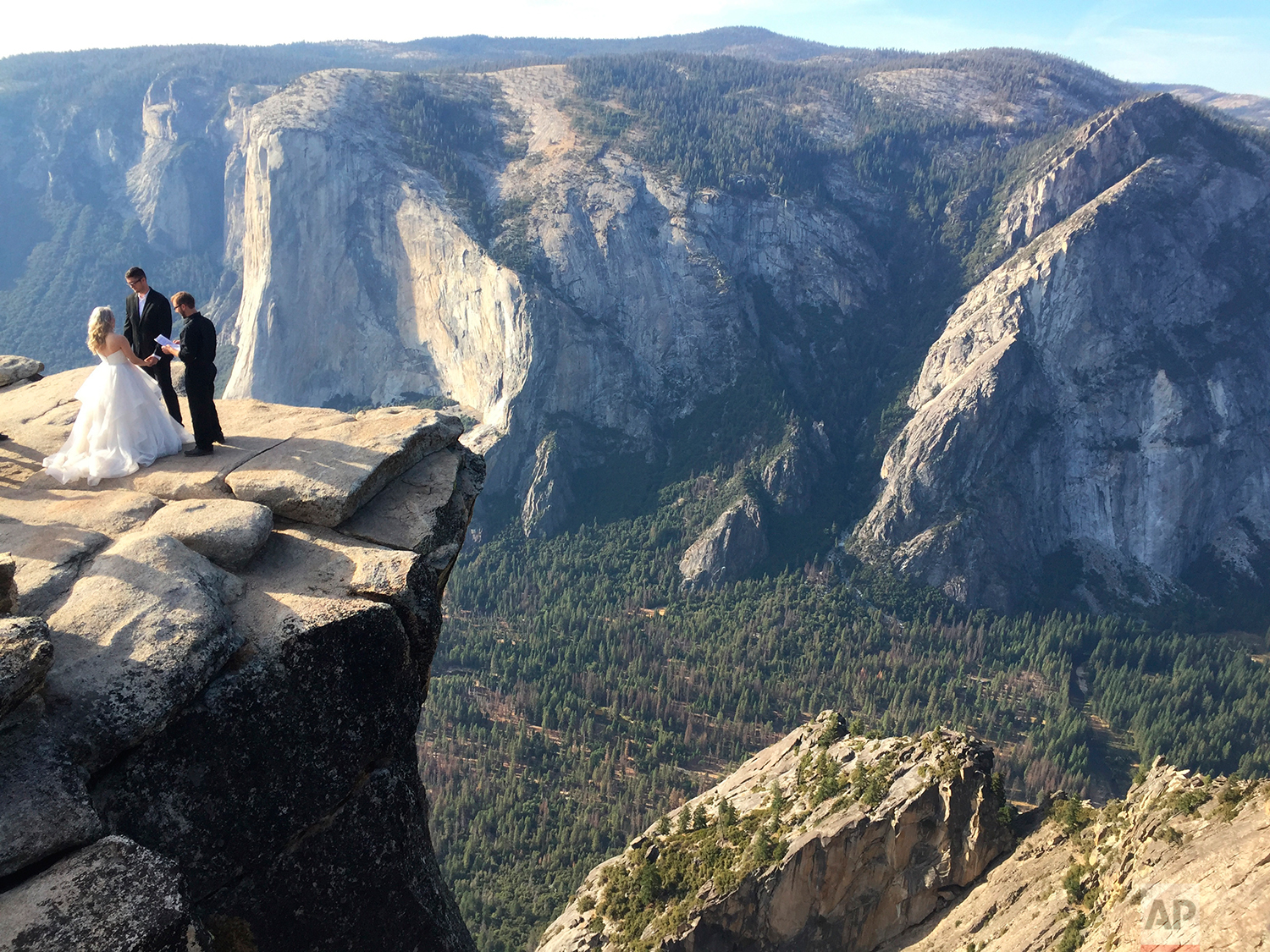A couple gets married at Taft Point in California's Yosemite National Park on Thursday, Sept. 27, 2018. The viewpoint overlooks Yosemite Valley, including El Capitan, a popular vertical ascent for rock climbers across the globe. (AP Photo/Amanda Lee Myers)