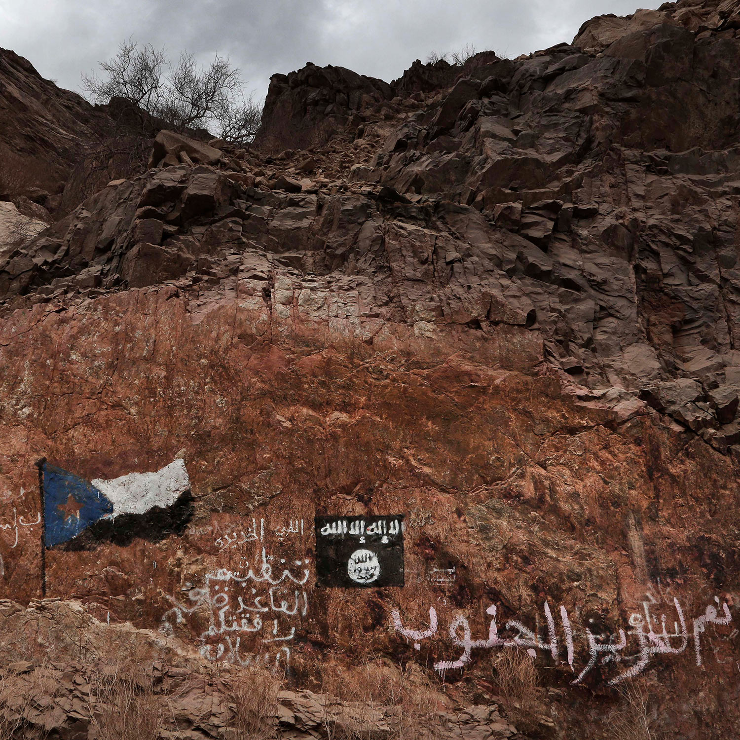 "This July 24, 2018 photo, shows the al-Qaida flag painted on rocks near the southern flag with Arabic that reads, ""Yes to liberating the south,"" and ""the Organization of al-Qaida: Have a Safe Trip,"" on a road in Shabwa, Yemen. (AP Photo/Nariman El-Mofty)"