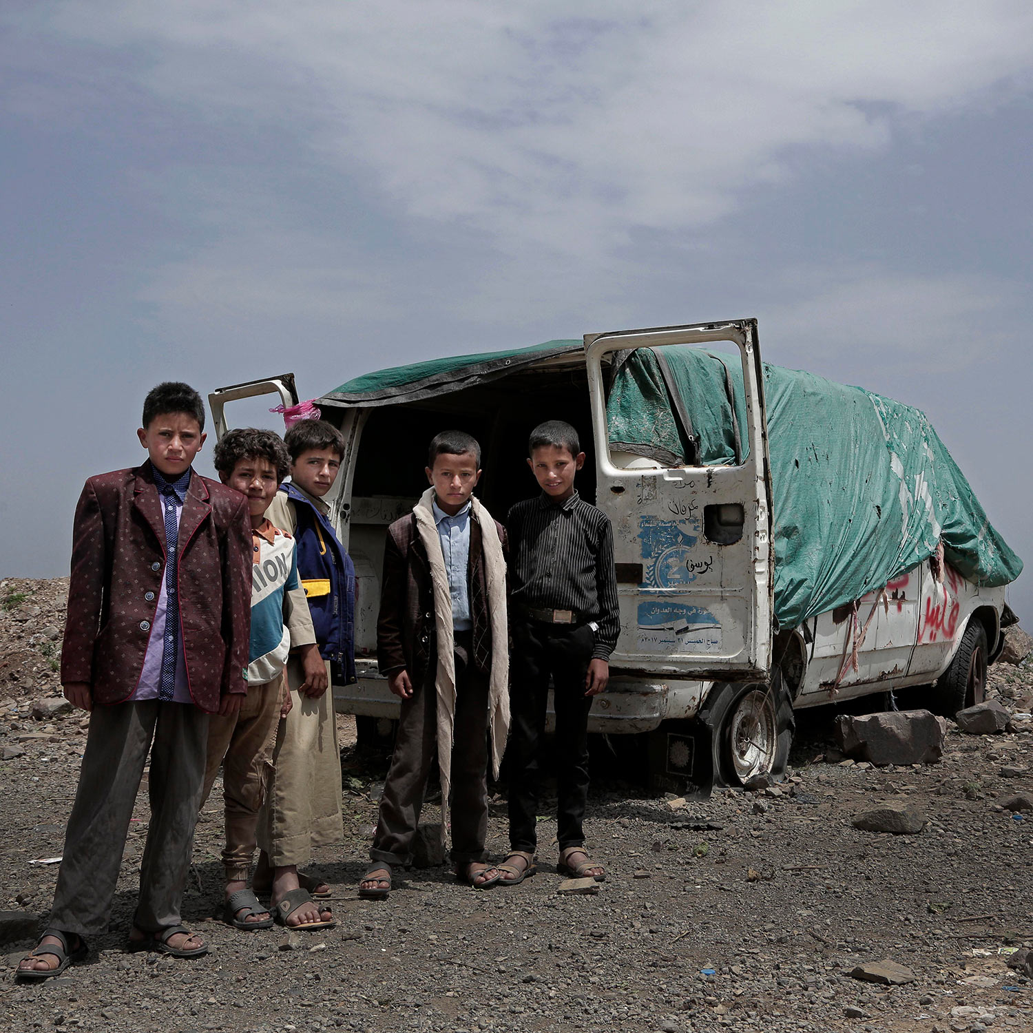 In this Aug. 3, 2018 photo, shows the dilapidated husk of a van behind them with four flat tires half sunk in the dirt on a mountain in Ibb, Yemen. (AP Photo/Nariman El-Mofty)
