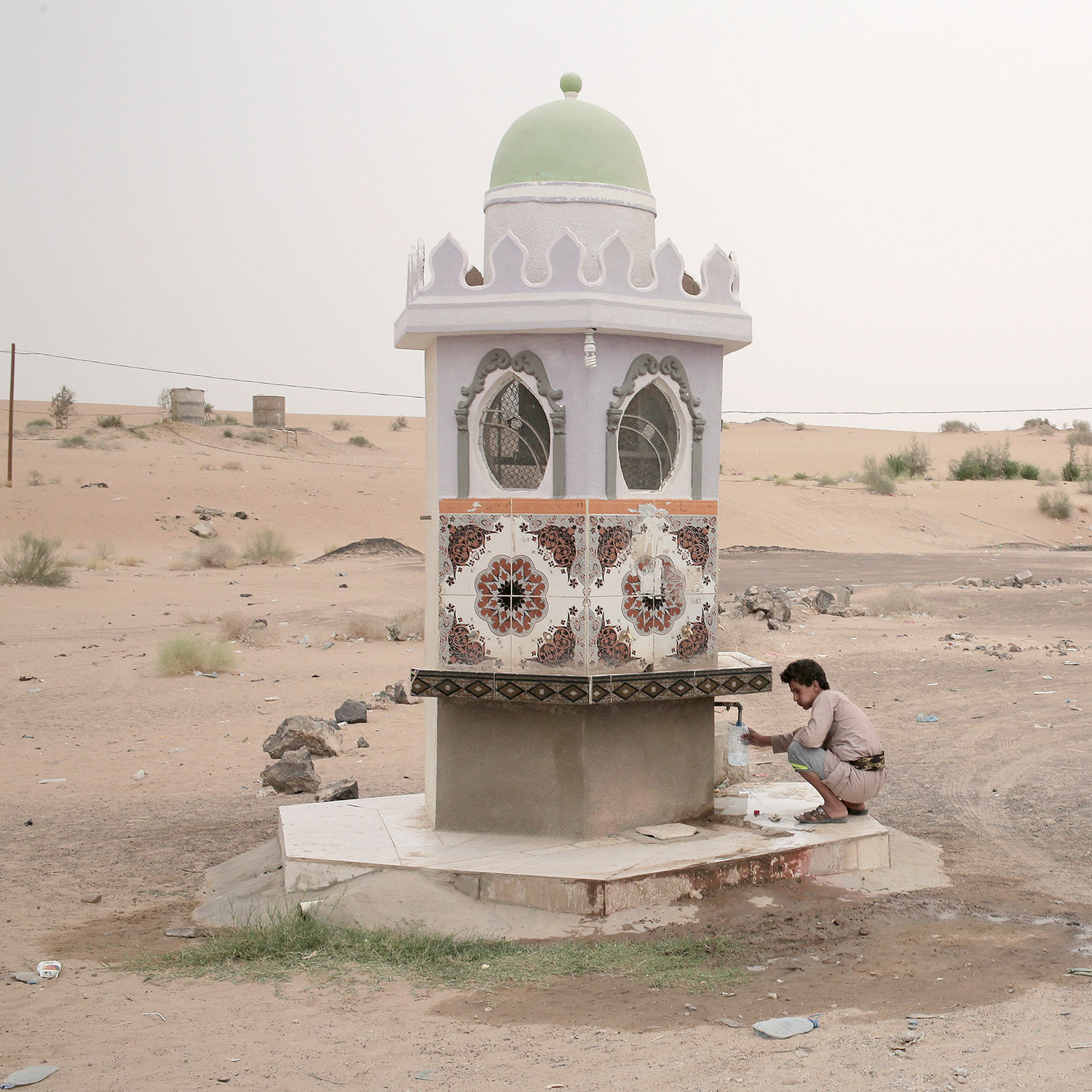 In this July 29, 2018 photo, a boy collects water from a fountain on a roadside in Marib, Yemen. (AP Photo/Nariman El-Mofty)