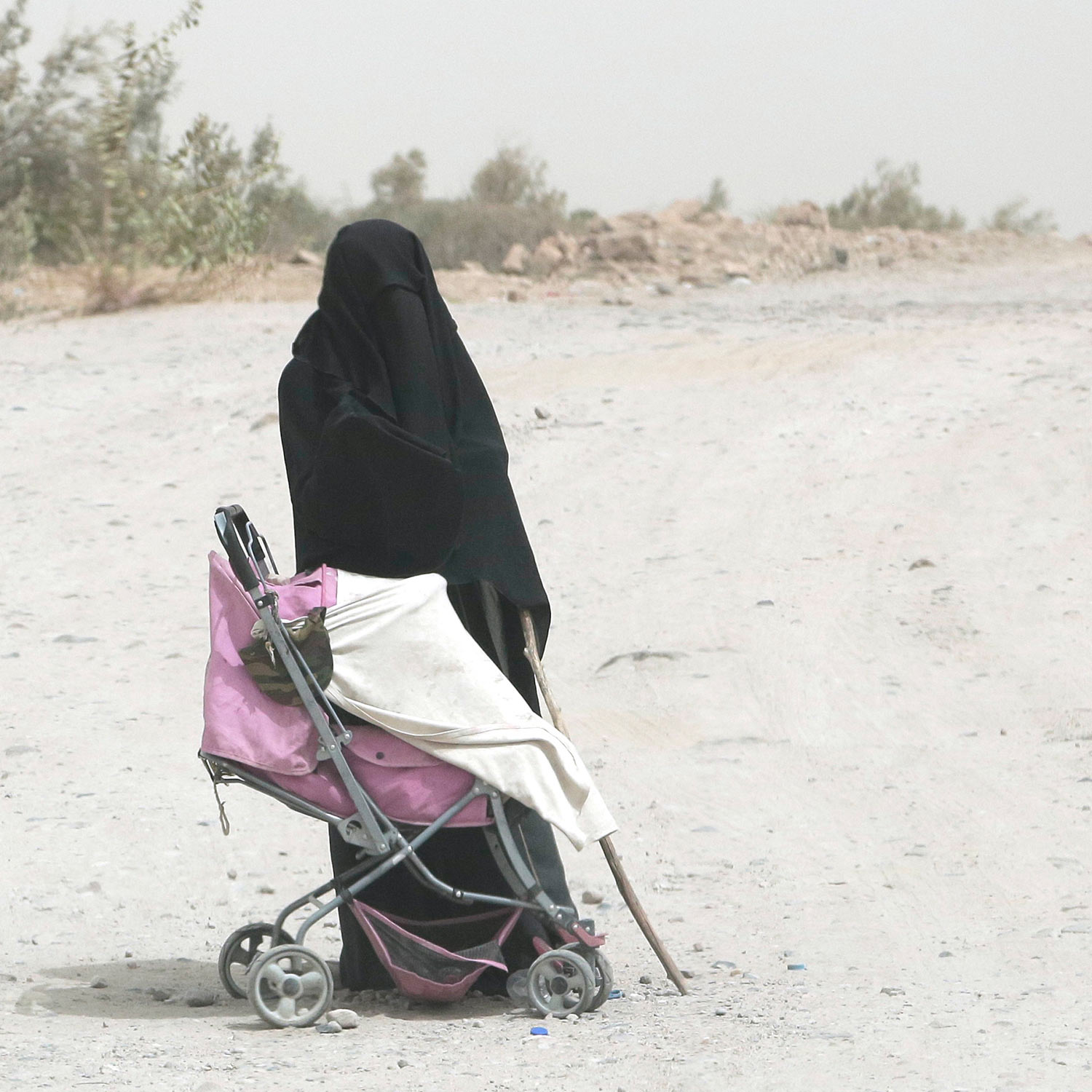 In this July 31, 2018 photo, a woman begs in the middle of a highway in Bayda province, Yemen. (AP Photo/Nariman El-Mofty)