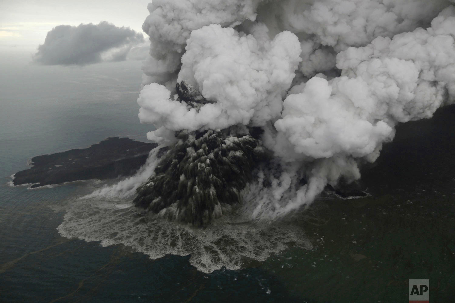 Plumes rise from Mount Anak Krakatau as it erupts in the Java Strait, Indonesia on Sunday, Dec. 23, 2018. A deadly tsunami followed an eruption and apparent undersea landslide on the volcano, gushing ashore without warning during a busy holiday weekend. (Nurul Hidayat/Bisnis Indonesia via AP)