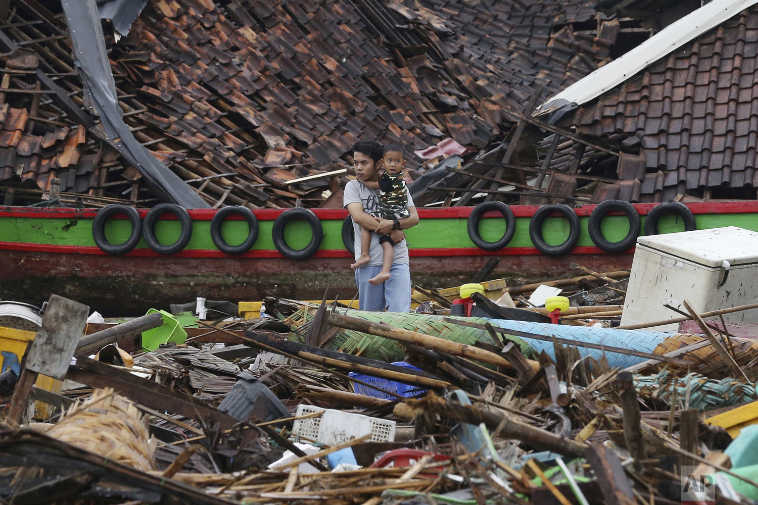 A man holds a child as he surveys the damage at a village struck by a tsunami in Sumur, Indonesia, Tuesday, Dec. 25, 2018. The waves struck without warning three days earlier. (AP Photo/Achmad Ibrahim)