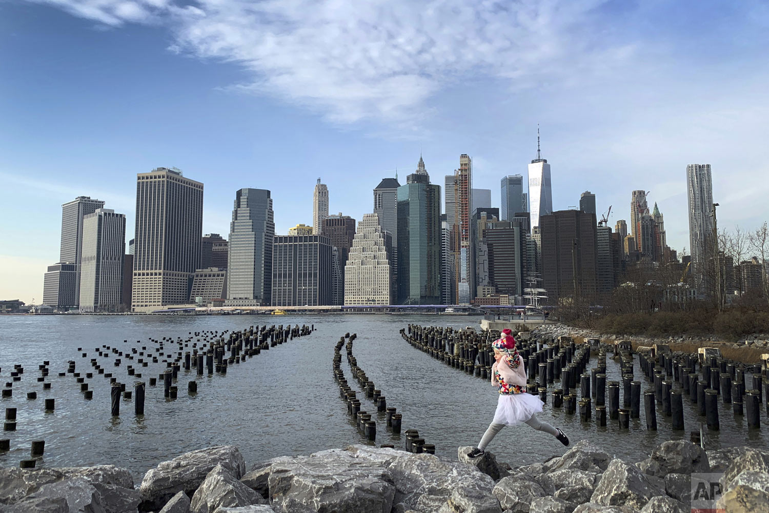 With downtown Manhattan in the background, a girl leaps across boulders forming a breakwater along the Brooklyn Bridge Park on Thursday Dec. 27, 2018, in the Brooklyn borough of New York. (AP Photo/Wong Maye-E)