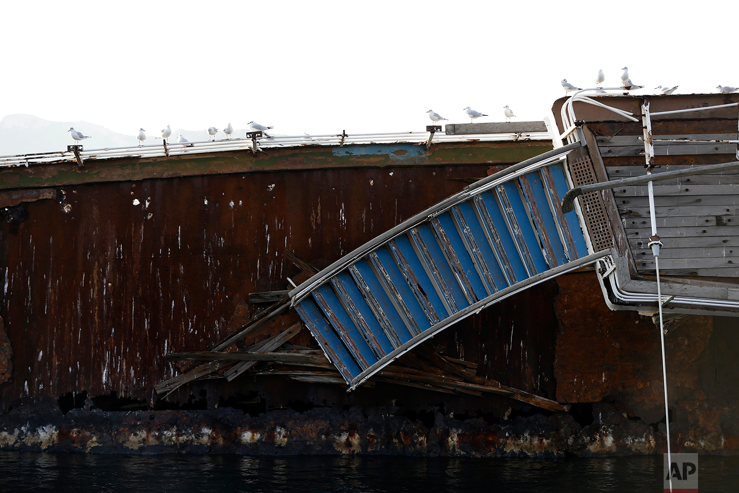 In this Friday, Dec. 4, 2018 photo, seagulls sit on a half sunken cruise ship in the Gulf of Elefsina, west of Athens. (AP Photo/Thanassis Stavrakis)