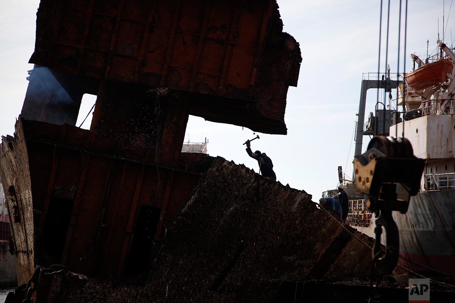 In this Monday, Nov. 5, 2018 photo, in a shipyard of Perama, west of Athens, workers cut up the rusted remains of a ferry that was recovered after spending years as a shipwreck. (AP Photo/Thanassis Stavrakis)