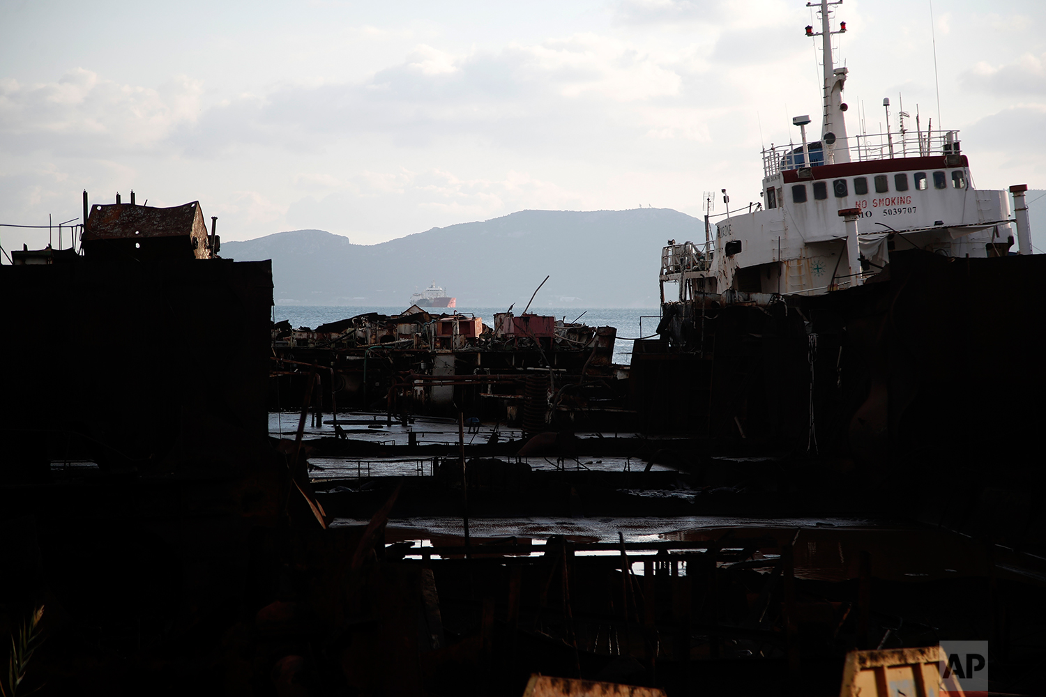 In this Wednesday, Dec. 19, 2018 photo, a cut tanker with crude oil, that was recovered after spending years as a shipwreck is photographed at a dock in Elefsina, west of Athens. (AP Photo/Thanassis Stavrakis)