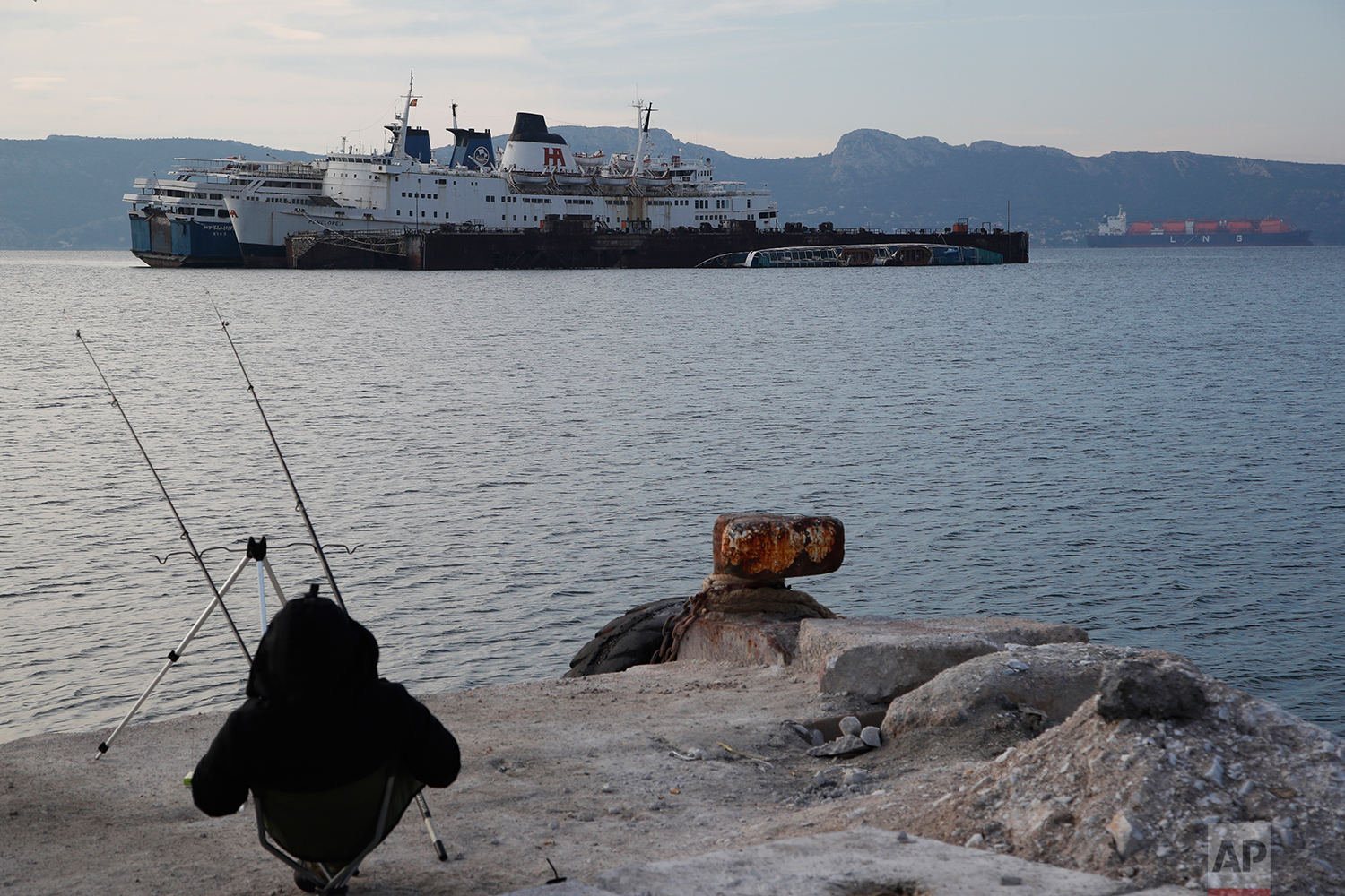 In this Friday, Dec. 4, 2018 photo, a man fishes as a half sunken and abandoned ships are moored in the Gulf of Elefsina, west of Athens. (AP Photo/Thanassis Stavrakis)