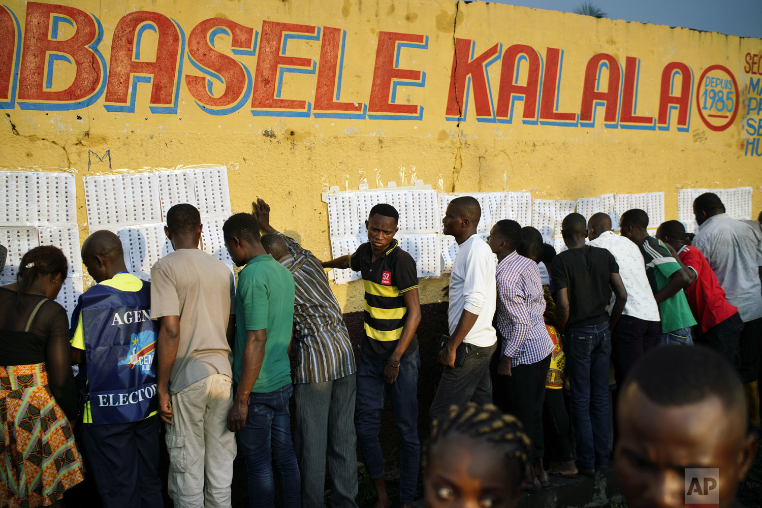 Election officials tape voter registration lists to a wall of the Les Anges primary school in Kinshasa, Congo, as voters start to check their names, Sunday Dec. 30, 2018. The election process was delayed when voters burned six voting machines and ballots midday, angered by the fact that the registrations lists had not arrived. Replacement machines had to be brought in, and voting started at nightfall, 12 hours late. Forty million voters are registered for a presidential race plagued by years of delay and persistent rumors of lack of preparation. (AP Photo/Jerome Delay)